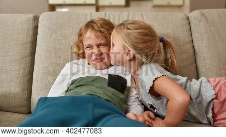 Portrait Of Little Boy Looking Disgruntled While His Sibling Sister Kissing Him On Cheek, Sitting To