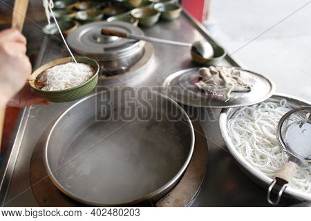 A Person Frying Noodles In A Wok High Quality Photo