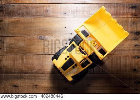 Toy Yellow Earthmover On A Wooden Background