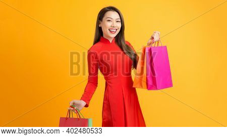 Happy Girl In Ao Dai Dress After Successful Shopping With Bags In Her Hands