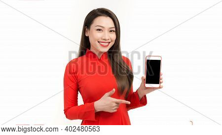 Portrait Of Asian Woman In Ao Dai Showing Or Presenting Mobile Phone Application And Pointing Finger