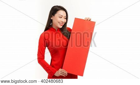 Beautiful Asian Woman On Traditional Festival Costume Ao Dai Holding Red Pocket. Tet Holiday. Lunar