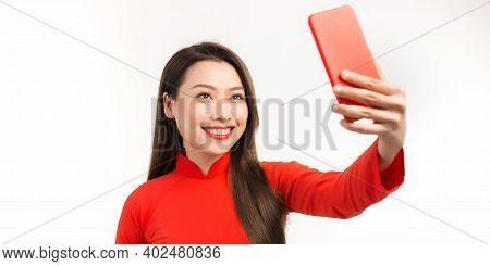 Woman Are Taking Posing For Mobile Phone, Wearing An Ao Dai. The Ao Dai Is The National Dress Of Vie