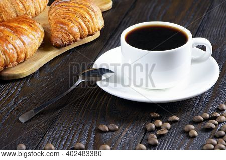 A Cup Of Hot Coffee And Croissants On A Wooden Background. Breakfast With Coffee And Fresh Pastry. C