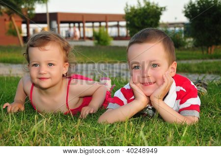 Little boy and girl happily on the grass.