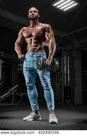 Pumped-up Man Posing In The Gym In Jeans With A Dumbbell In His Hand. Sports, Bodybuilding, Powerlif