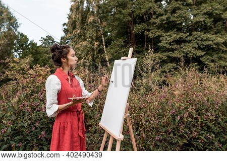 Beautiful Woman In Red Dress White Shirt, In Summer Park Forest, Draws A Picture, White Canvas Paint