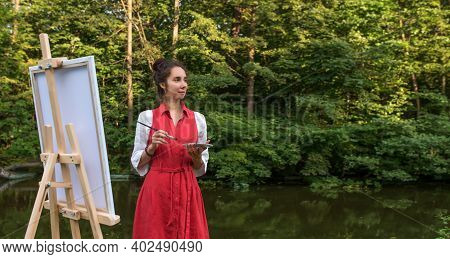 Beautiful Woman In Red Dress Lake River Pond, In Summer In Park Forest, Draws Picture, Creating Land