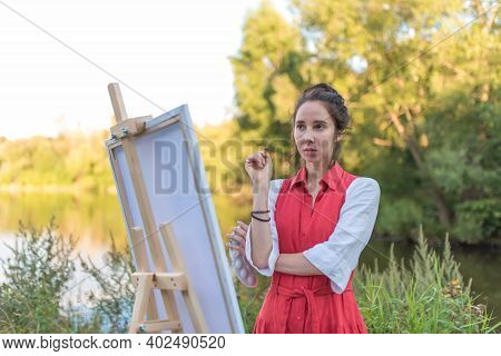 Beautiful Woman In Red Dress By Lake, River Pond, In Summer Park Forest, Draws Picture, Creating A L