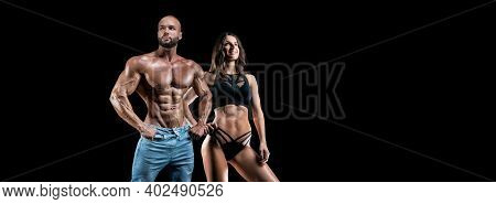 Muscular Man And Woman Posing Against A Black Background. Bodybuilding And Fitness Concept.