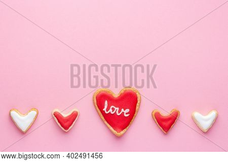 A Row Of Heart Shaped Cookies With Sugar Icing And Word Love For St Valentine Day On Pink Background