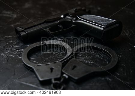 Pistol And Handcuffs On Black Textured Table. Ammunition Of Law Enforcement Agencies. Firearms For T