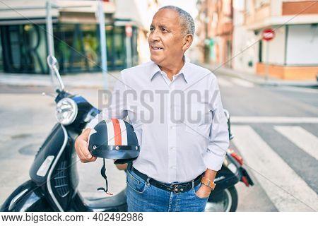 Senior motorcyclist man smiling happy holding moto helmet at the city.