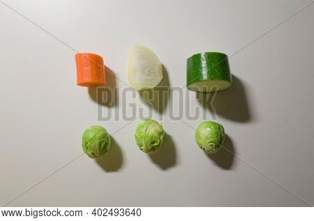 Vegetables pieces isolated on white table surface background. Healthy organic raw cut vegetables top view. Zucchini, brussels sprouts, onion, carrot. Flat lay with dark shadow