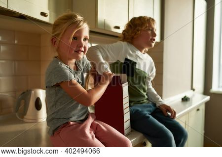 Portrait Of Cute Little Girl Looking Aside, Eating Cornflakes While Sitting On The Kitchen Cabinet T