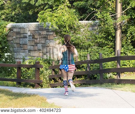 Rear View Of A Female Runner Running In American Flag Shorts And Socks On A Tar Path In A Park.