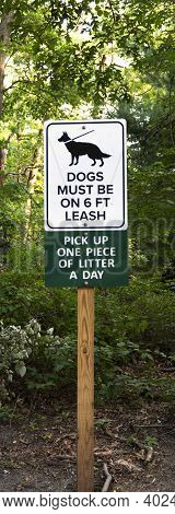 Dogs Must Be On Six Fool Leash Sign Andpick Up One Piece Of Litter A Day Sign On A Post In The Woods