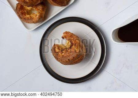 A Single Yorkshire Pudding Viewed From The Top Down Sitting On A Black Rimmed Plate On A White Backg