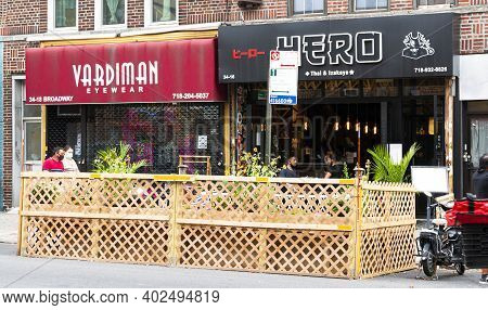 Astoria, New York, Usa - 30 July 2020: People Eating At Tables Placed In City Street Surrounded By W