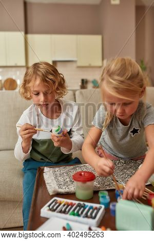Adorable Little Boy Painting Colorful Easter Eggs Together With His Sibling Sister, Sitting On A Cou