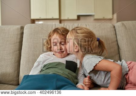 Gentle Kiss. Portrait Of Cute Little Girl Kissing Her Sibling Brother While Spending Time Together,