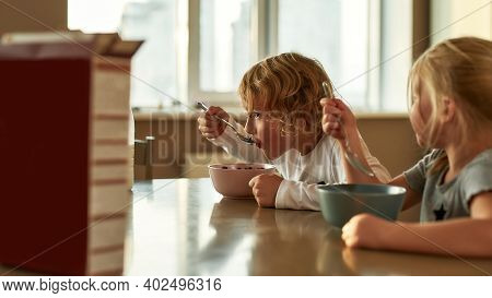 Cute Little Children Eating Chocolate Cereal With Milk For Breakfast While Sitting Together At The T
