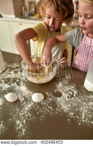 High Angle View Of Little Siblings, Boy And Girl In Aprons Helping Each Other Whille Preparing Dough
