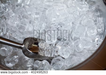 Ice Cubes In A Bucket. Ice Shovel. Ice Scoop On The Ice Cubes Background, Top View With Copy Space A