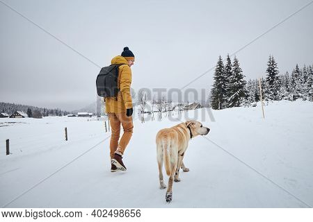 Rear View Of Young Man With Dog In Winter. Pet Owner With His Labrador Retriever Walking Against Old
