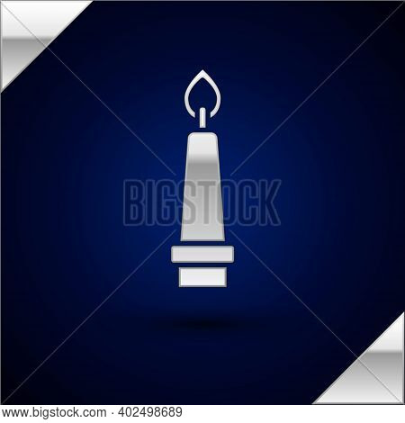 Silver Burning Candle In Candlestick Icon Isolated On Dark Blue Background. Old Fashioned Lit Candle