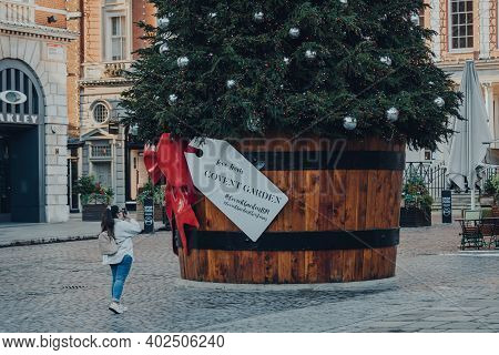 London, Uk - November 19, 2020: Woman Taking Photo On Mobile Of A Giant Christmas Tree In A Pot In F