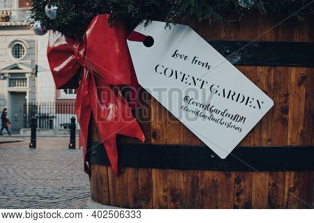London, Uk - November 19, 2020: Close Up Of A Gift Tag On A Giant Christmas Tree In A Pot In Front O