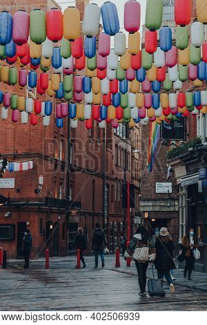 London, Uk - November 19, 2020: People Walk Under Rainbow Coloured Lanterns On A Street In Chinatown