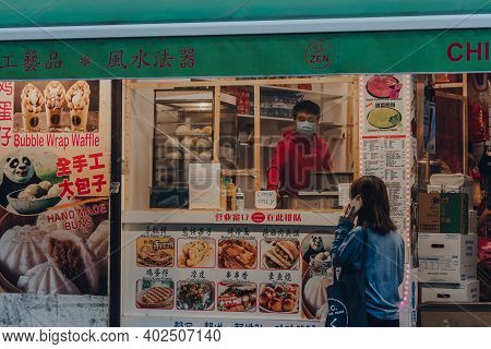 London, Uk - November 19, 2020: Woman Ordering Take Away From A Restaurant In Chinatown, An Area Of