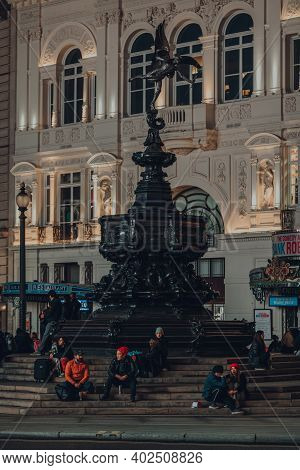 London, Uk - November 19, 2020: Few People Sitting On The Steps Of Eros Statue In Piccadilly Circus,