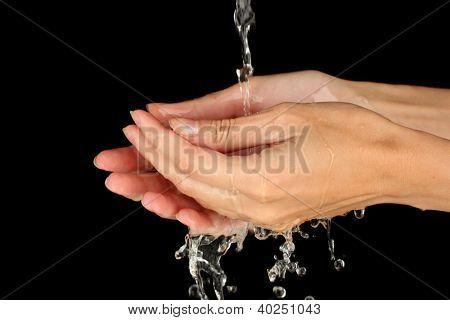 Washing hands on black background close-up