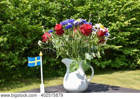 Summer Flowers And A Swedish Flag At A Table Decoration