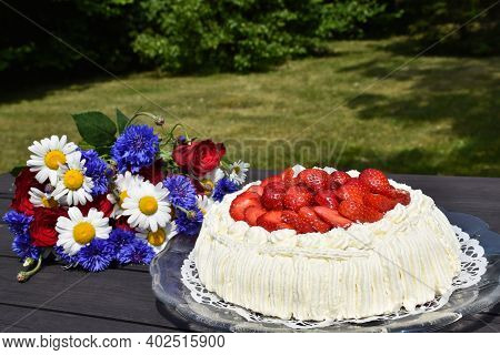 Summer Flowers And Yummy Cream Cake On A Table In A Sunlit Garden