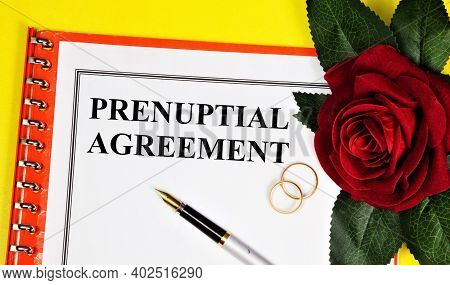 Prenuptial Agreement. Text Inscription On The Form Of The Document. Wedding Rings And Red Rose Holid