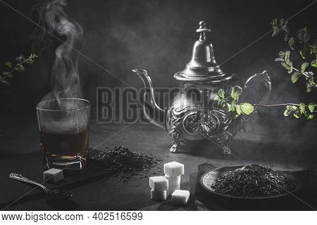 Traditional Moroccan Teapot, With A Steaming Cup Of Tea, Sugar And Mint, In A Smoky Black Atmosphere