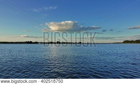 Wide Calm River With Blue Water. There Are Beautiful Cumulus Clouds In The Azure Sky. In The Distanc