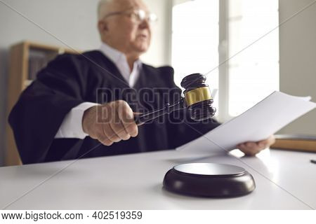 Judge Holding Gavel, Hitting Sound Block And Pronouncing Sentence In Court Of Law