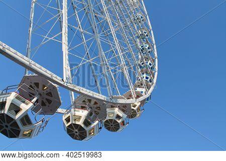 Funfair Ferris Wheel On Blue Sky Background. Selective Focus
