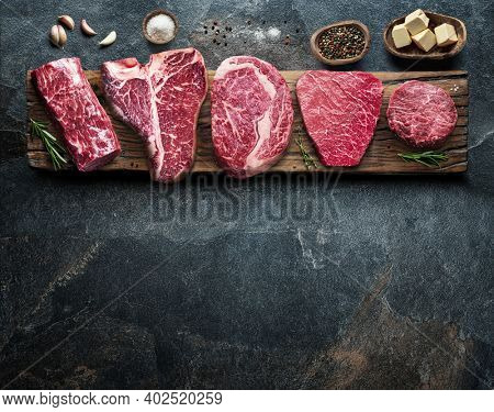 Different raw beef steaks on the wooden board on the grey table. Top view.