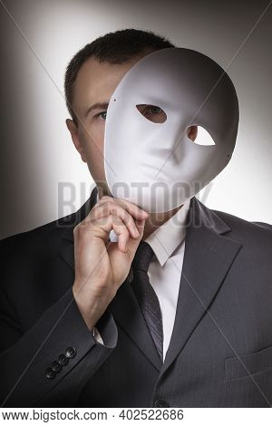 Man Covering His Face With A Mask. Concept On The Topic Of Secrecy Of The Person.
