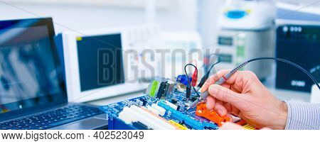Repair motherboard in electronics laboratory. Technological background with closeup on tester checking motherboard.