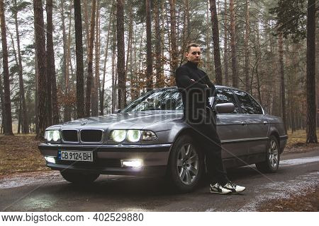 Chernigov, Ukraine - January 6, 2021: A Guy Stands Near A Bmw 7 (e38) Car On The Road In The Forest.