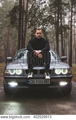 Chernigov, Ukraine - January 6, 2021: A Guy Sits On The Hood Of A Bmw 7 (e38) On The Road In The For