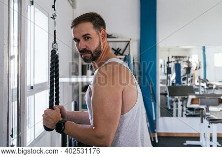 Man In A Gym Making Triceps With Ropes. Gym Concept