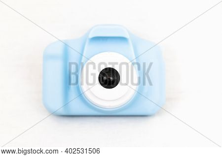 A Blue Toy Childs Digital Camera With White Background Using Selective Focus On The Lens.